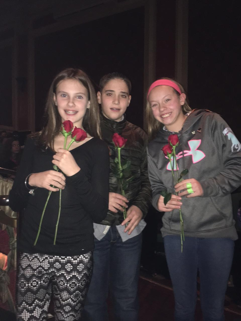 Caleigh Morrow, Michael Glynn, and Brooke Keen present roses to the actors.